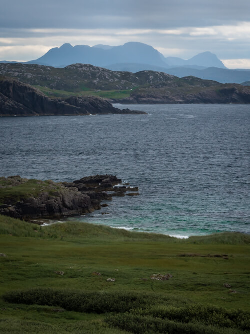 Blue waters with green marsh and tall Assynt hills in the distance, Scotland