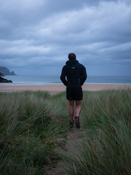 A man walks through the grass dunes at Kearvaig Beach