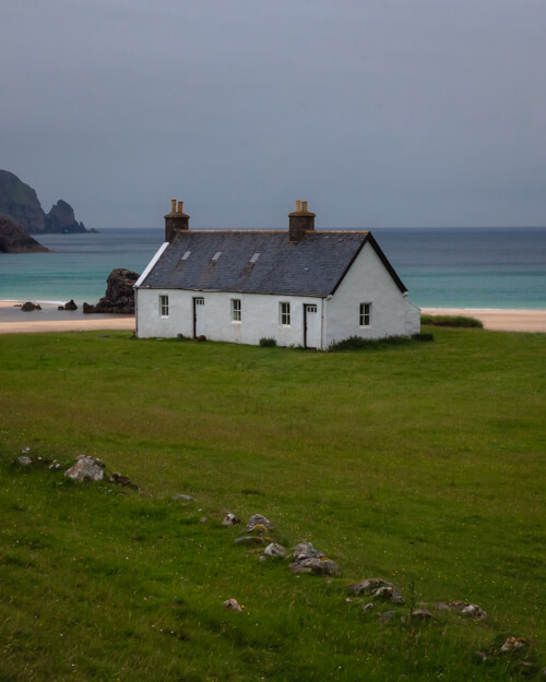 A white bothy on a grassy mound above the beach at Kearvaig, Scotland