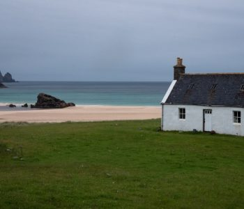 A white bothy on grass land with a beach and blue sea in the background