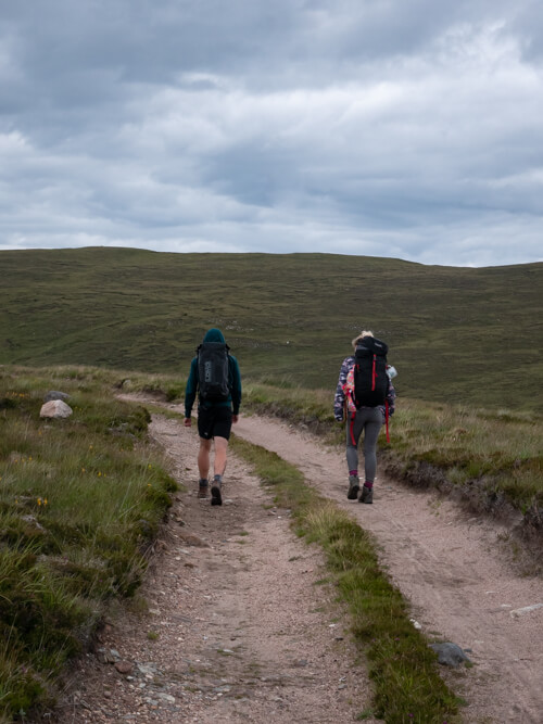 Two backpackers walking down a rough road in marshland
