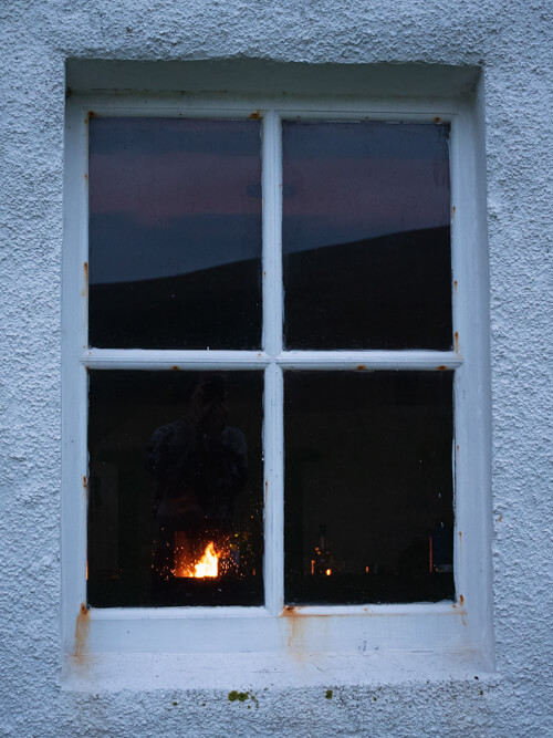 A window from the outside, with the glow of fire inside