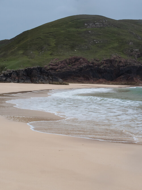 Water laps the white sands of Kearvaig Beach with a green hill in the distance