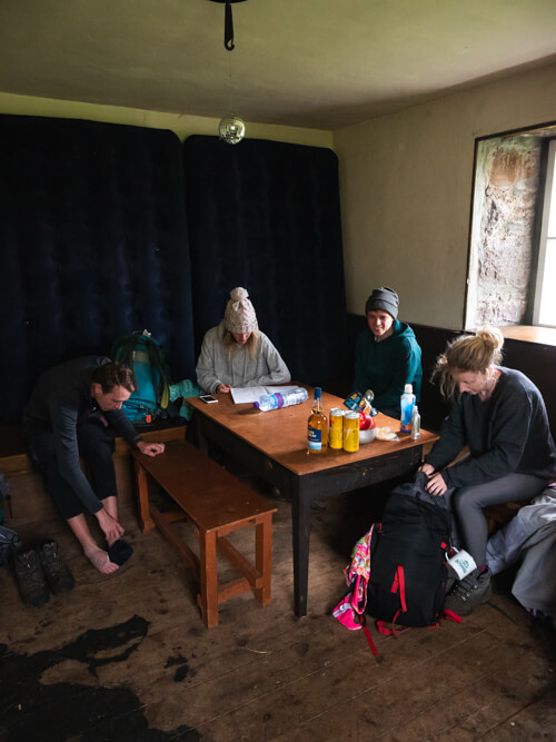 A group sit around the table inside a bothy