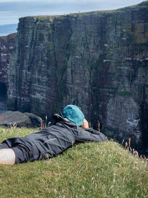 A man lying prostate uses binoculars to spot birds