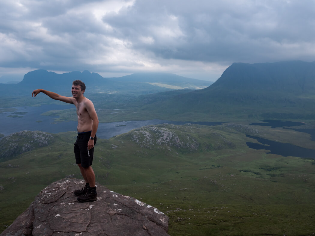 A man stands on a ledge of Stac Pollaidh with Assynt hills in the background