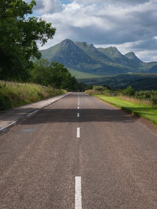 A road with Scottish highland mountains in the distance