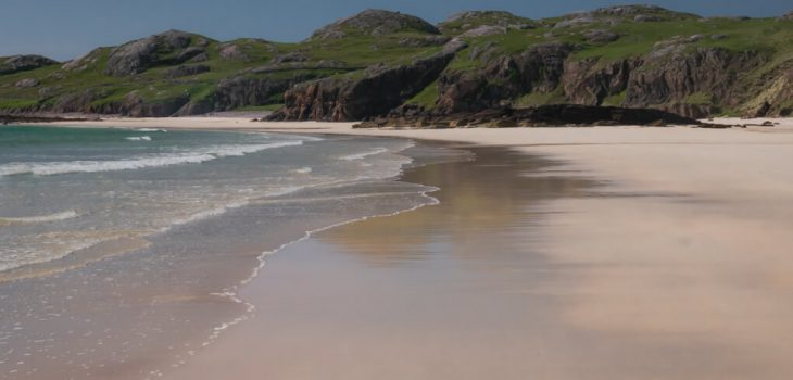 Water laps white sand with highland hills in the background, Oldshoremore Beach, Scotland
