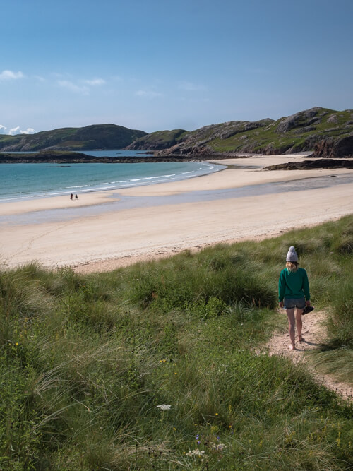 A girl walks down the grassy dunes to Oldshoremore Beach, Scotland
