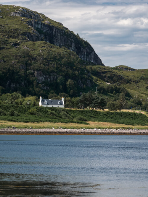 A white cottage sits on green grass above a loch near Poolewe