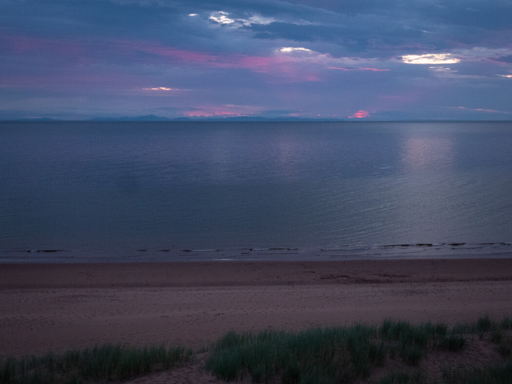Pink and purple skies as sun sets on Red Point Beach
