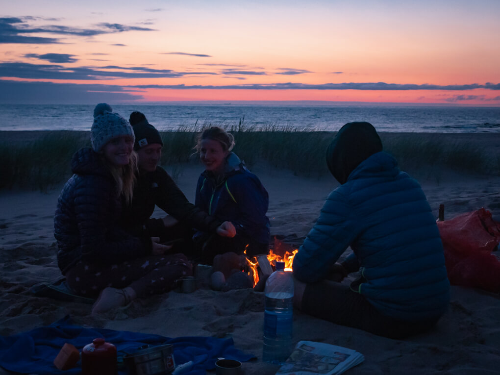 Campers sit around a campfire on Sandwood Bay during sunset