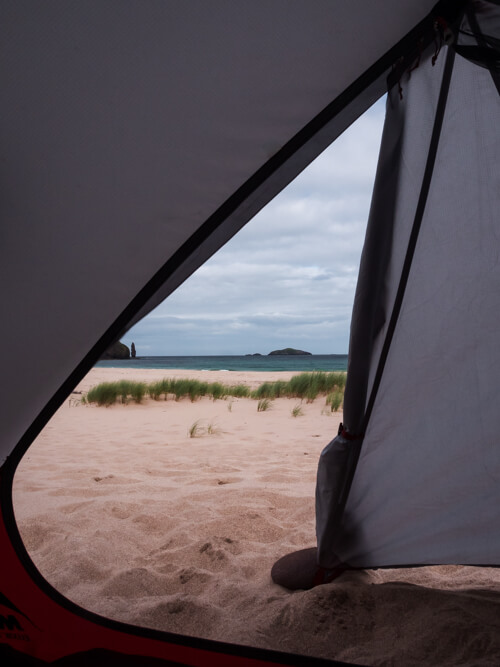 The open door of a tent on Sandwood Bay
