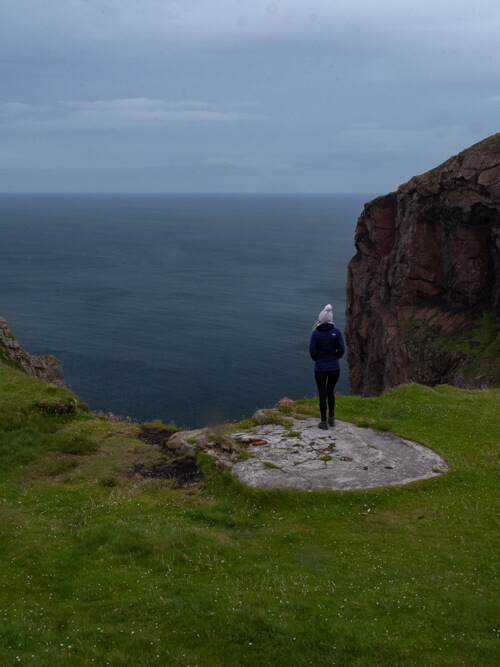 A girl stands with her back to the camera staring out to sea at Cape Wrath, Scotland
