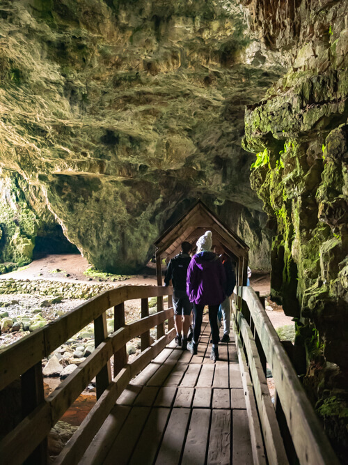 People walking over a bridge in Smoo Cave, Durness