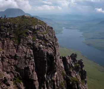Walkers sit on a high ledge at Stac Pollaidh with loch in the distance