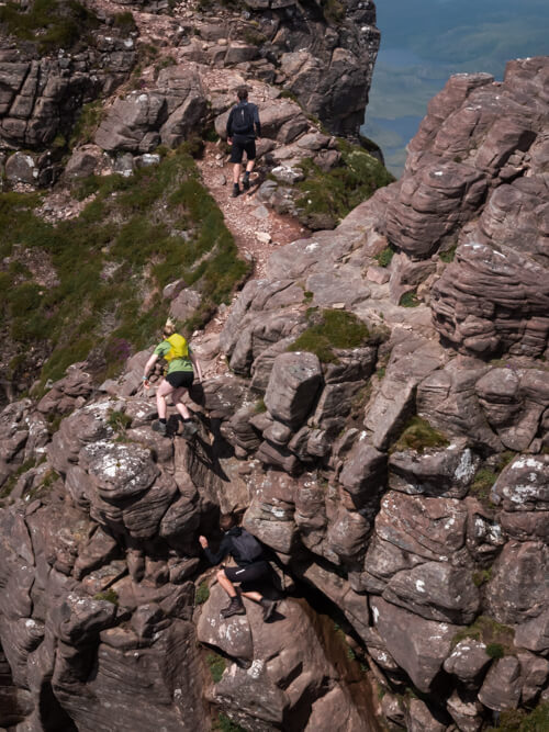 A group of climbers clamber over rocks on Stac Pollaidh