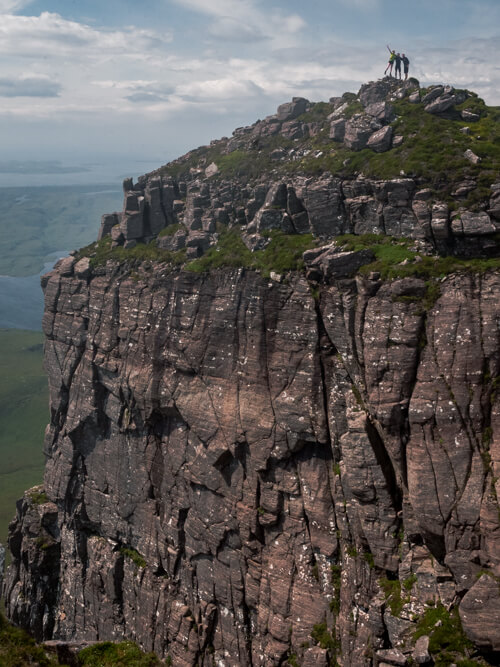A group of hikers celebrate at the top of a craggy hill in Scotland