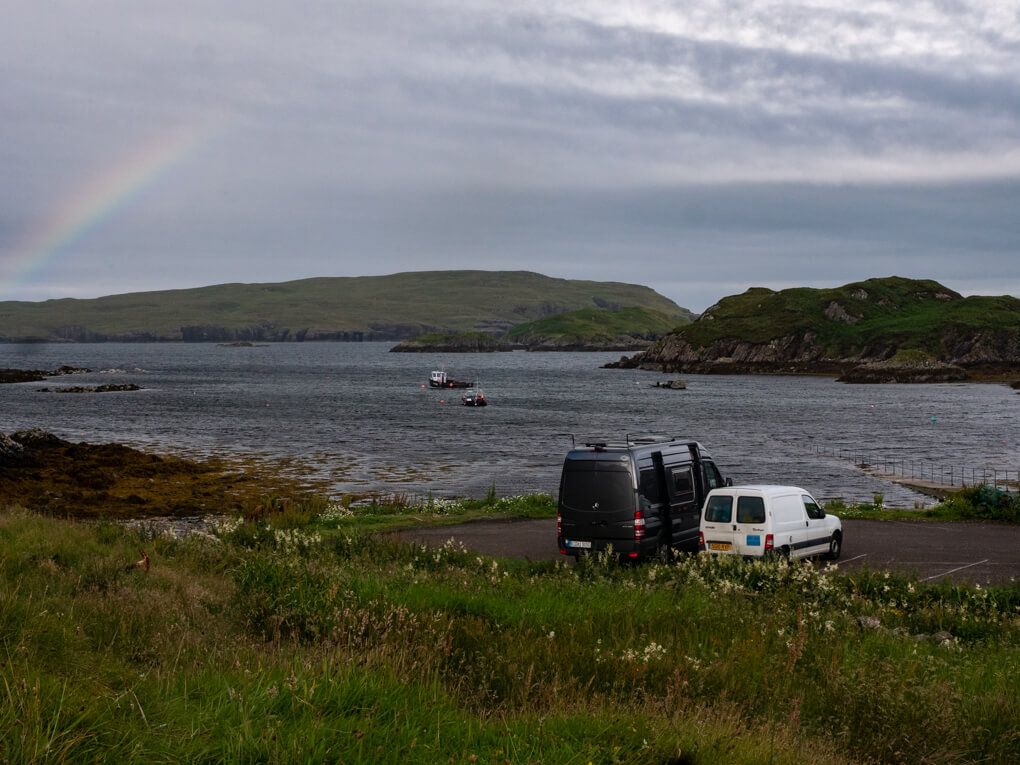 A couple of cars are parked at Tarbet Pier with Handa Island in the background