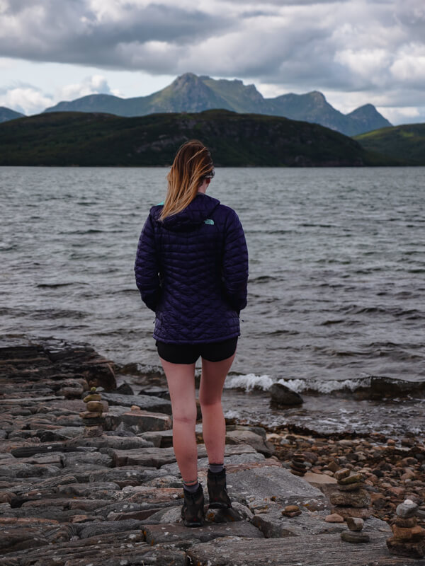 A girl stands with her back to the camera at Loch Hope, Tongue, Scotland