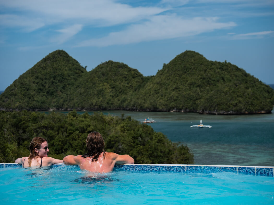 A couple enjoy an infinity pool with a sea view, Sipalay