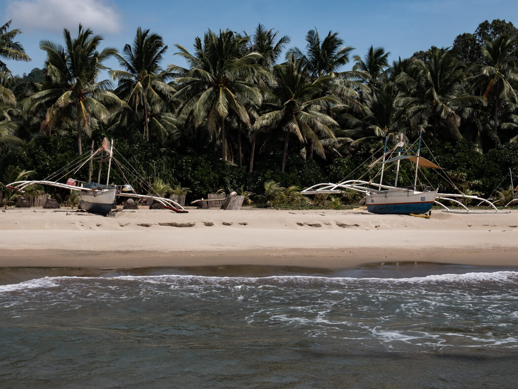 A view of the sand from the water, with boats on the sand and trees in the background, Sipalay