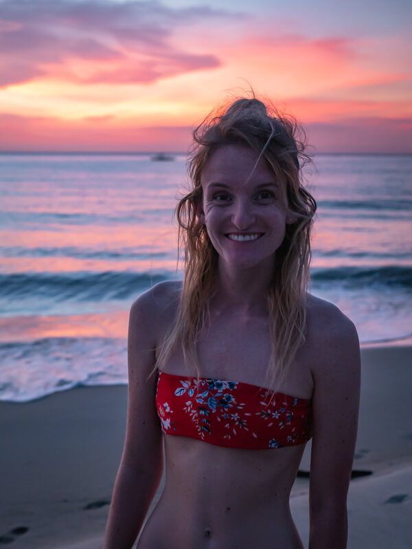 A girl smiles during sunset on Sugar Beach