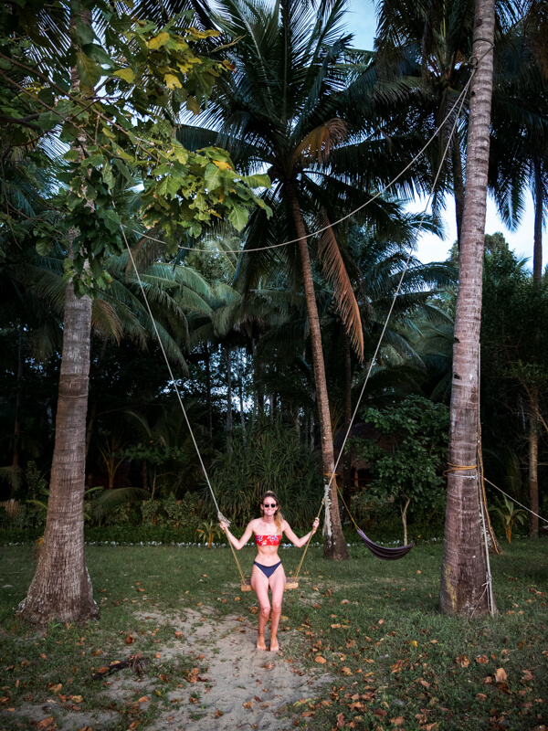 A girl sits on a swing between palm trees on Sugar Beach