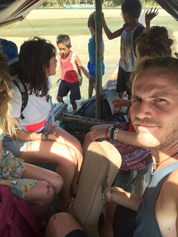 A man looks confused on a small boat with local children