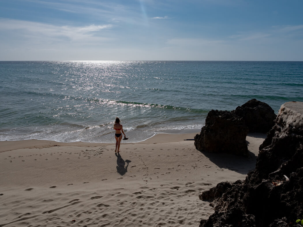A girl walks in to the Sugar Beach sea with rocks nearby