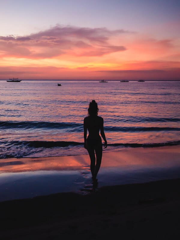The silhouette of a girl with sunset in the background on Sugar Beach