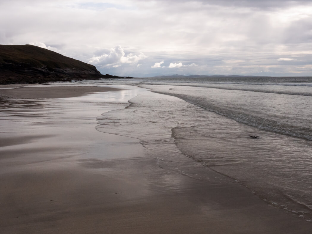 Waves lap up on to the sand at Allt a Chamais beach, Scotland