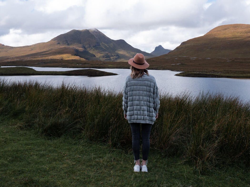 A girl stands in front of lochs, cloud and hills near Knockan Crag, Scotland