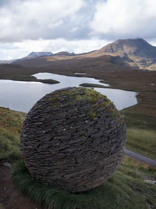 A slated spherical display stands on a hill side, with hills and lochs in the distance, Assynt