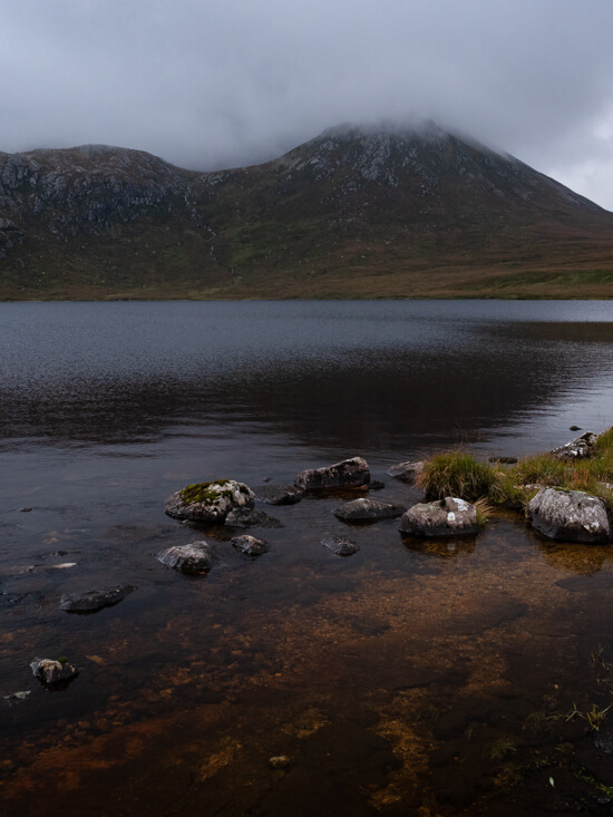 Murky waters of Loch na Gainmhich with cloud above the hills