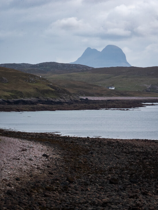 A house sits below Suilven with water on its shores