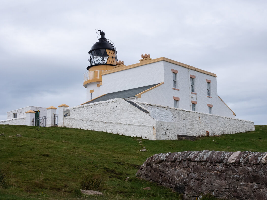 Stoer Lighthouse, with yellow details on a bright white building