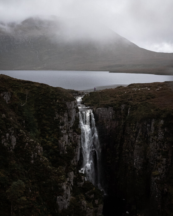 A girl stands above a waterfall with loch and mountains in the background