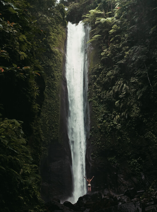 A girl stands beneath a powerful waterfall, Negros
