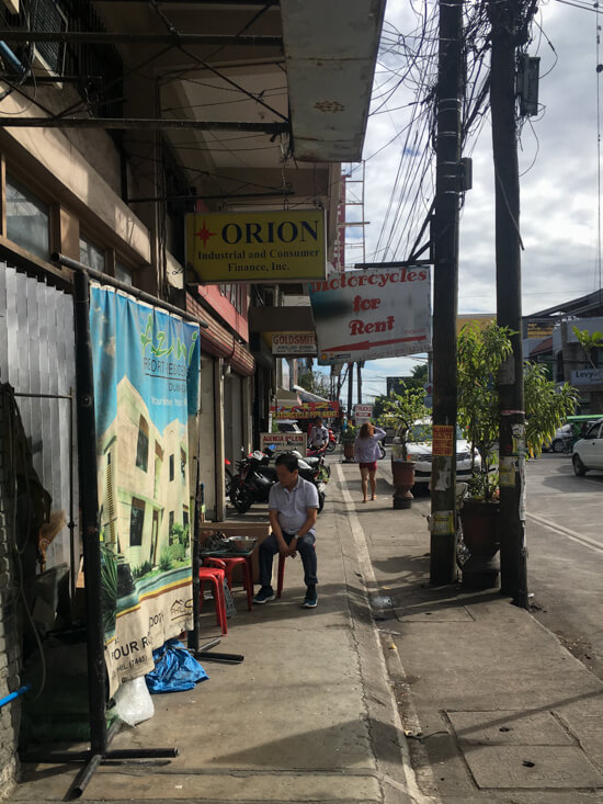 A sign says 'motorcycle for rent' on a street in Dumaguete