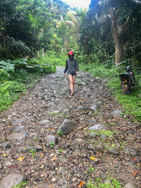 A girl walks down a gravel, rough road in Negros