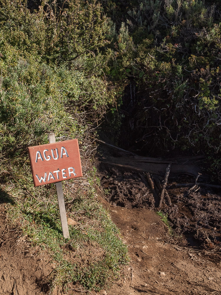 A sign 'agua water' leads to a fresh water source on Cerro Castillo