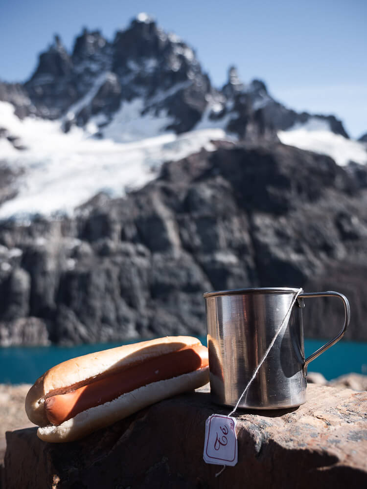 A hot dog and a mug of tea with Cerro Castillo in the background