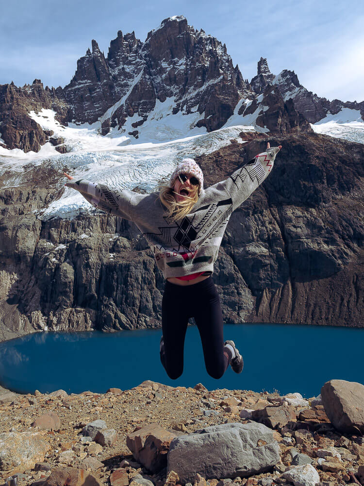 A girl jumps in front of Cerro Castillo with a big smile on her face