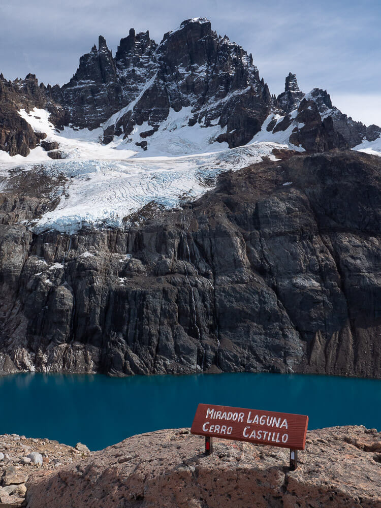 A sign reads 'Mirador Laguna Cerro Castillo' in front of blue water and below the peak