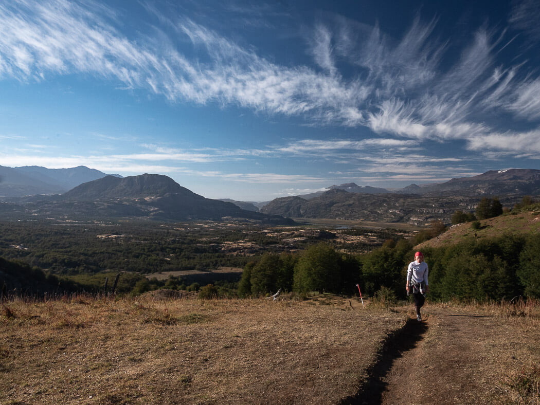 A girl walks up Cerro Castillo with gorgeous views of Aysen behind her