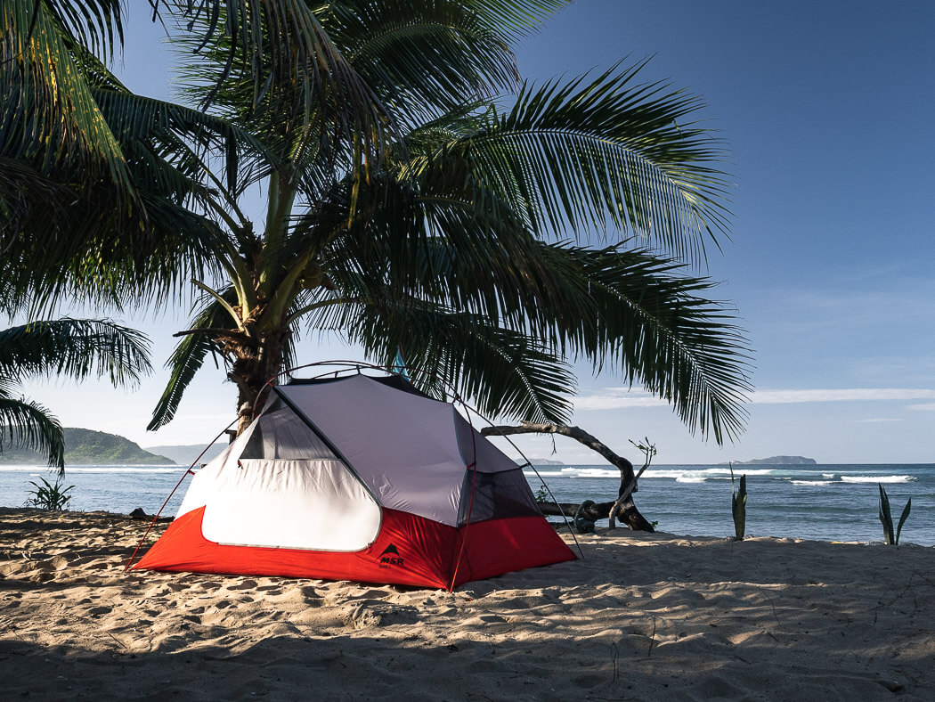 A tent on white sand with waves rolling in the background