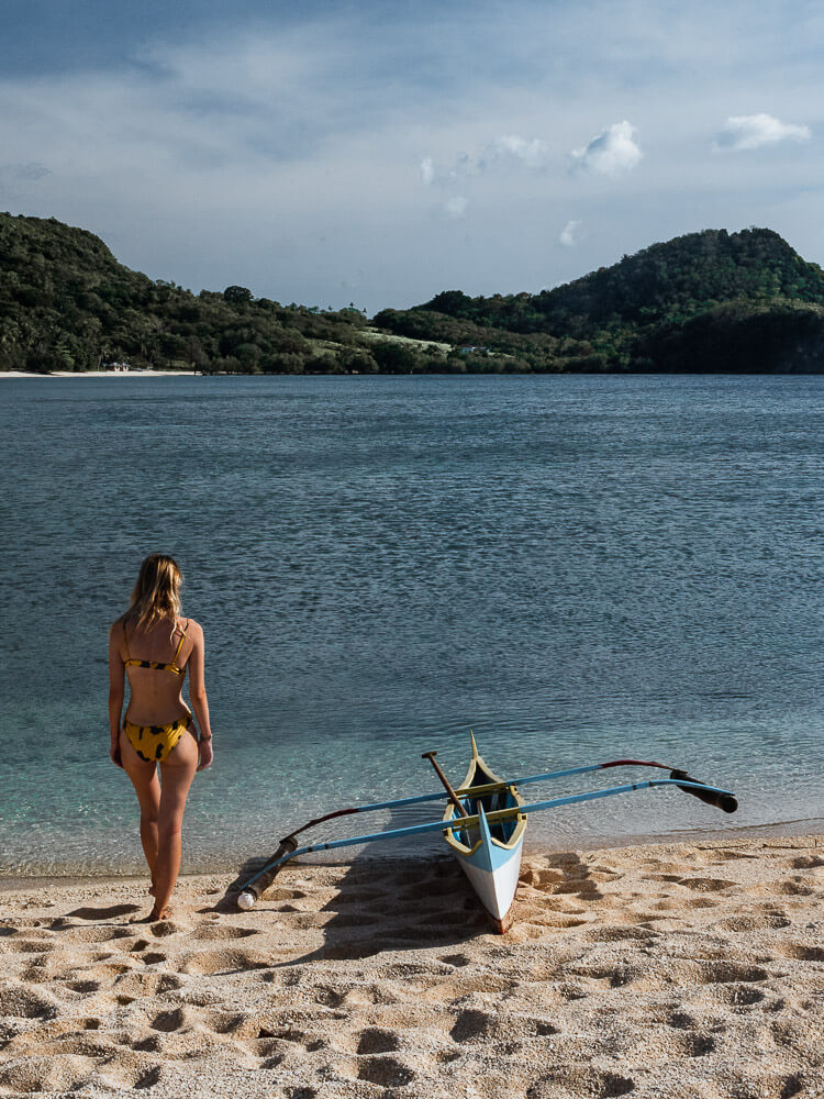 A girl stands next to a boat on Binucot Beach