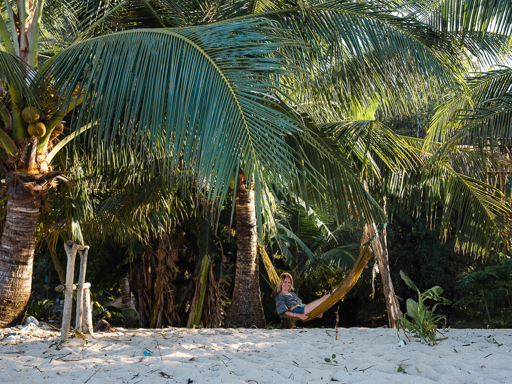 A girl sits on a hammock underneath a palm tree