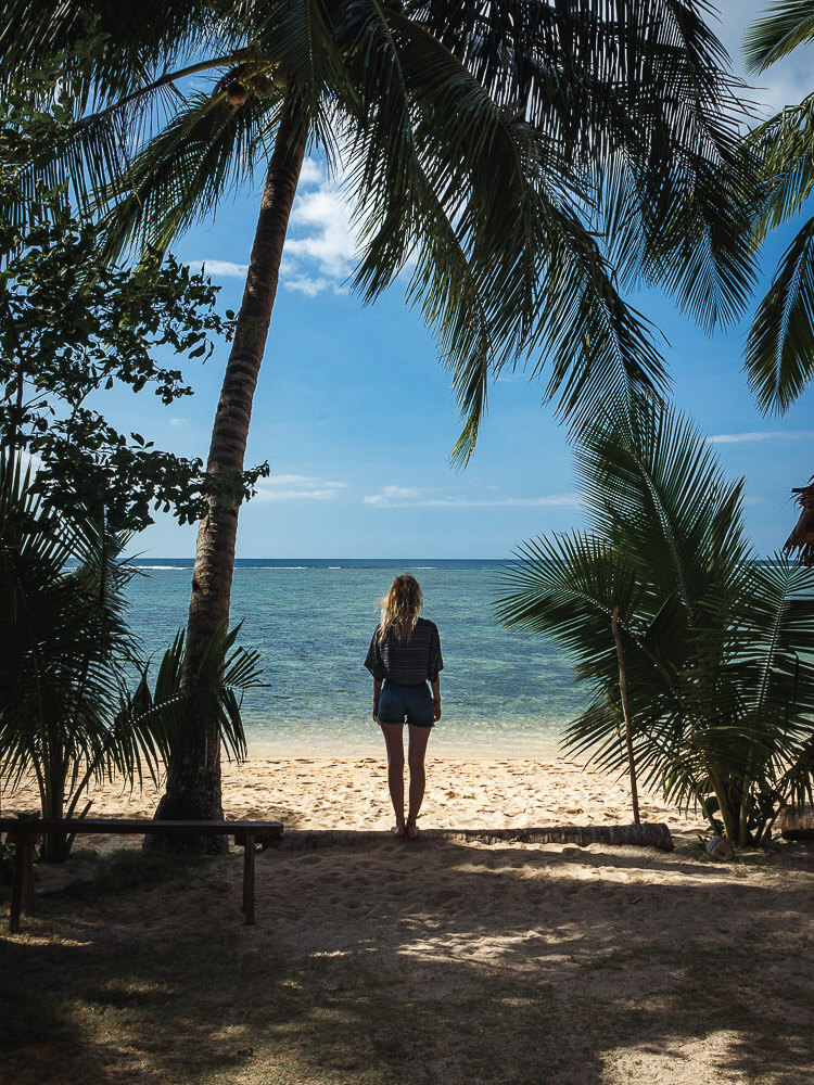 A girl stands on a beach with palm trees surrounding her. 3 Weeks Philippines Itinerary
